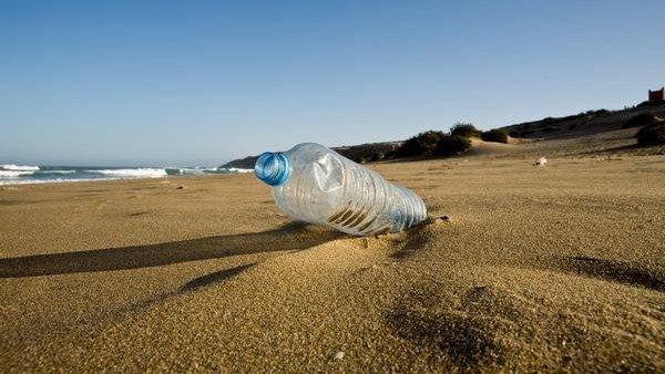 Botella de plástico en la arena de la playa